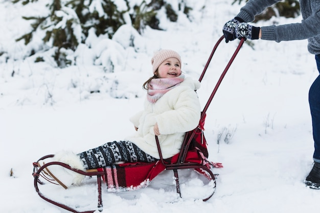 Laughing girl riding sleigh with father