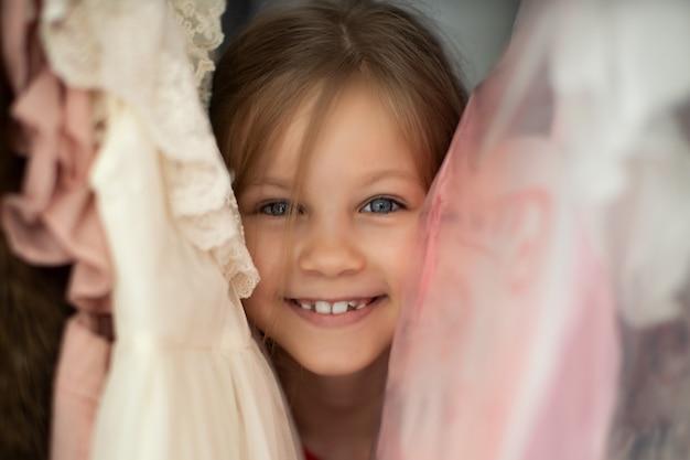 ドレスをハンガーの間に立っている笑っている女の子