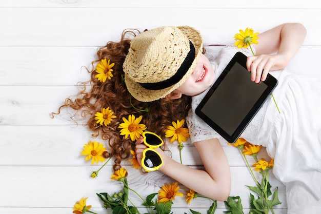 Laughing girl in a straw hat resting on the tablet in her hands. dreaming of a rustic town.