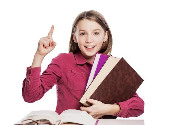 メガネで笑っている女の子のティーンエイジャーは、本のテーブルに座っています。知識と教育。 。