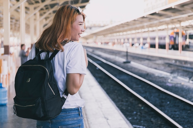 Laughing girl with backpack on railroad