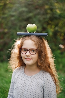 Laughing girl with a book and apple on his head.