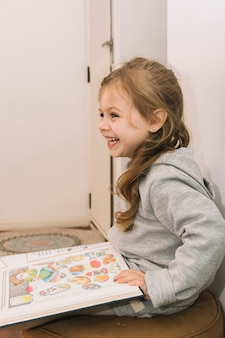 Laughing girl with book on pouf