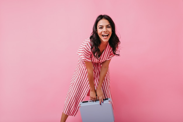 Laughing girl with dimples on cheeks emotionally posing for full-length portrait with blue luggage.