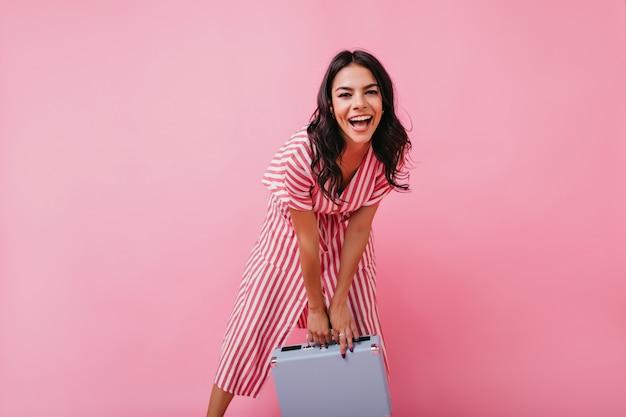 Смеющаяся девушка с ямочками на щеках эмоционально позирует портрету в полный рост с синим багажом.