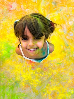 Laughing girl with paint stained her face. child laughs happily enjoying active games and creativity.