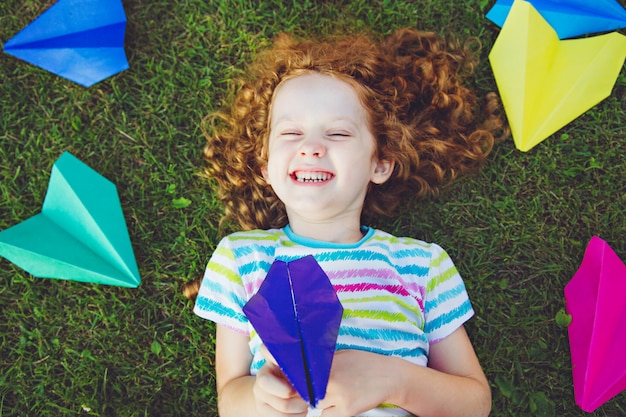 Laughing girl with paper airplane in her hand on green lawn.