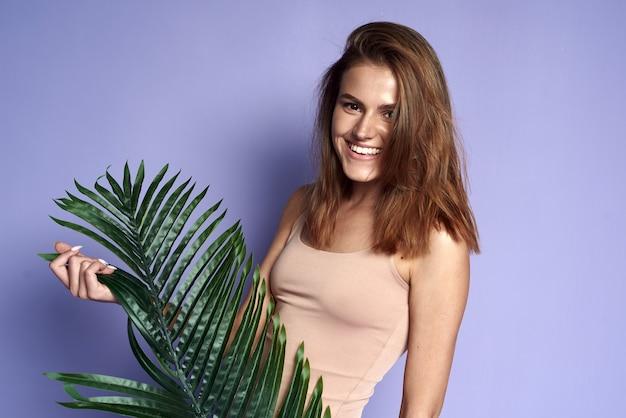 紫色のスタジオで熱帯の葉を持つ笑う女の子。明るい笑顔で美しいブルネットの夏の肖像画。