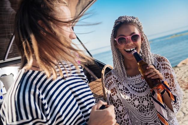 笑うガールフレンド。彼氏とリラックスしながら笑っているピンクのサングラスを身に着けているドレッドヘアを持つスタイリッシュなガールフレンド