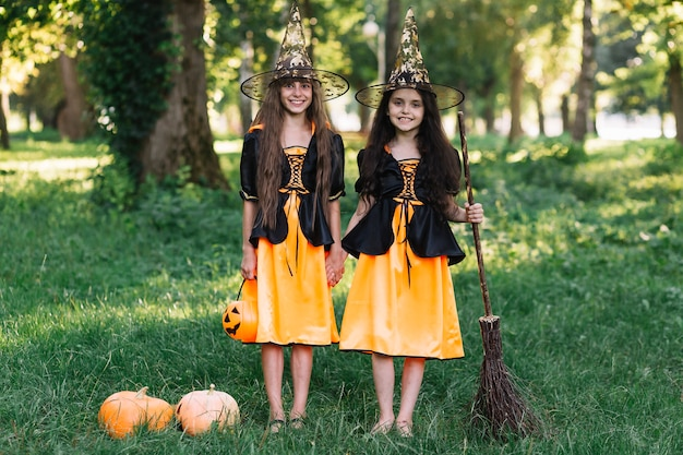 Laughing girls in witch costumes holding hands, broom and pumpkin