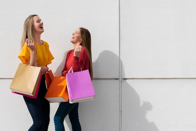 Laughing girls with shopping bags