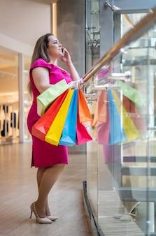 現代のブティックモールで紙の買い物袋とスマートフォンを話す魅力プラスサイズの女性を笑う