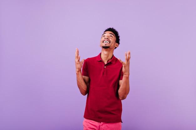 見上げるイケメンを笑う。赤いシャツのポーズで幸せな男性モデル。