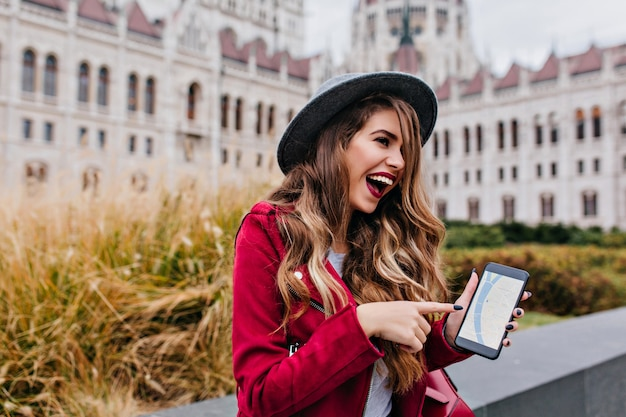 Laughing gorgeous woman in hat showing phone screen while exploring old part of city
