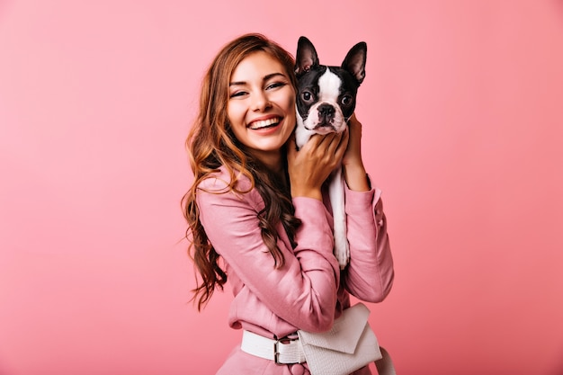 Laughing gorgeous woman holding her puppy. portrait of ginger cute girl posing on pink with french bulldog.