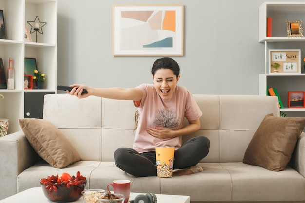 Laughing grabbed stomach young girl holding tv remote sitting on sofa behind coffee table in living room