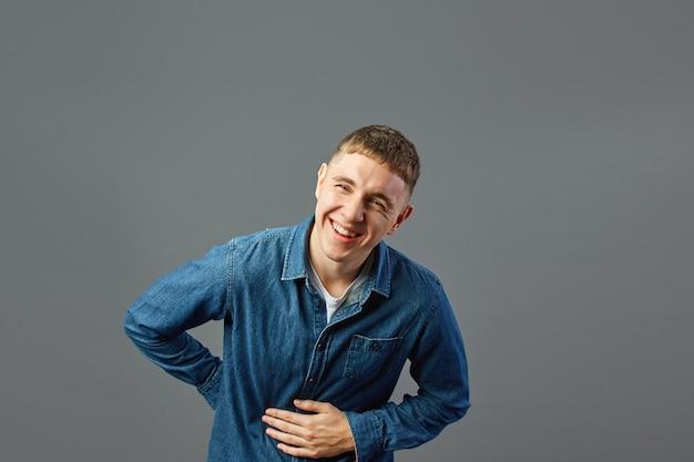 청바지 셔츠를 입은 웃고 있는 남자는 회색 배경에 있는 스튜디오에서 뱃속에 손을 얹고 있습니다.