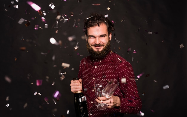 Laughing guy with bottle and glasses between confetti