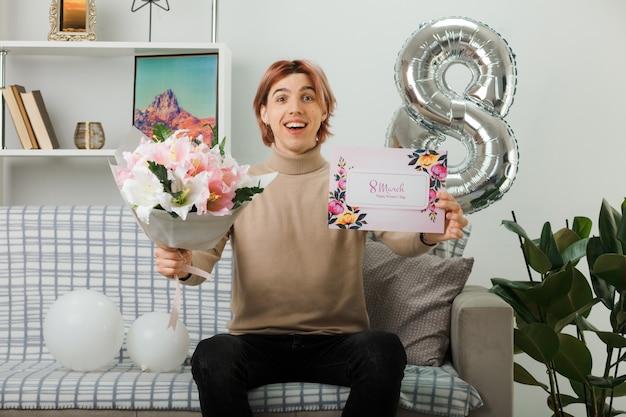 Bel ragazzo che ride durante la giornata delle donne felici che tiene bouquet con biglietto di auguri seduto sul divano in soggiorno
