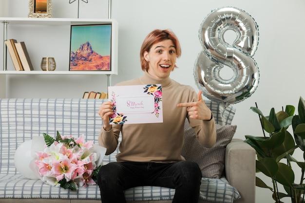 Ridere bel ragazzo durante la giornata delle donne felici che tiene e indica il biglietto di auguri seduto sul divano nel soggiorno