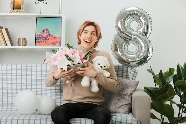 リビングルームのソファに座っているテディベアと花束を持って幸せな女性の日にハンサムな男を笑う