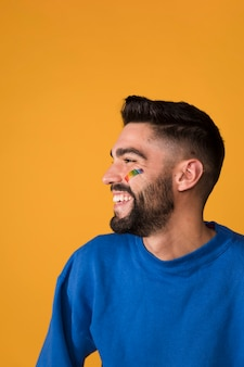 Laughing handsome man with lgbt rainbow on face