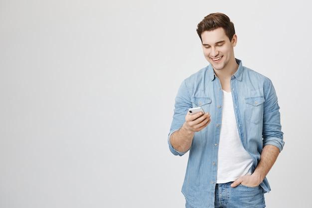 Смеющийся счастливый парень улыбается мобильному телефону, обмен сообщениями