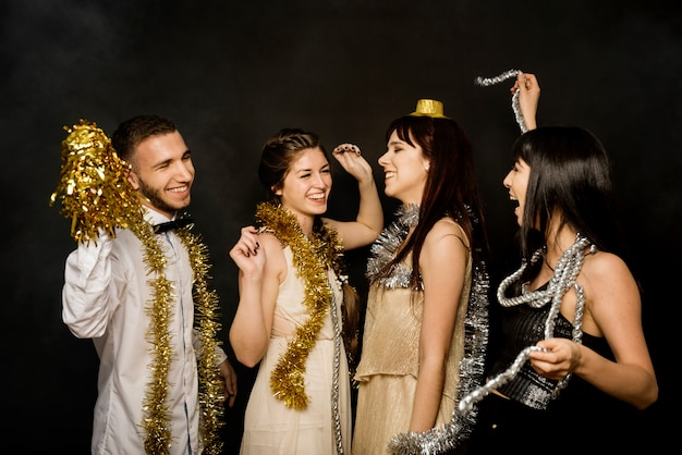Laughing happy ladies and guy in evening cloths with tinsel