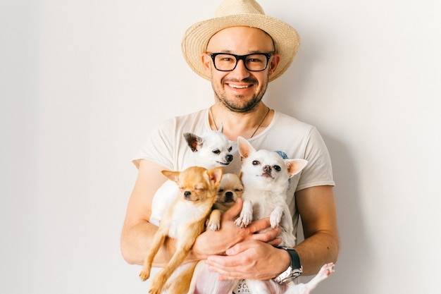 Laughing happy man in straw hat hugs four little chihuahua puppies