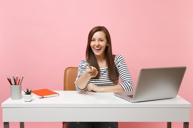 Смеющаяся счастливая женщина, указывающая карандашом на передней, сидит за белым столом с современным ноутбуком