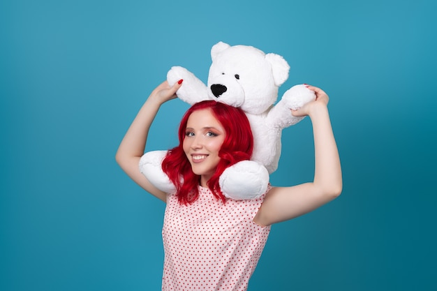 Laughing happy  woman with red hair and a huge teddy bear on her shoulders