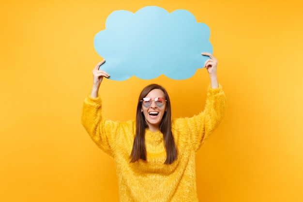Laughing happy young woman in heart eyeglasses holding empty blank blue say cloud, speech bubble isolated on bright yellow background. people sincere emotions, lifestyle concept. advertising area.