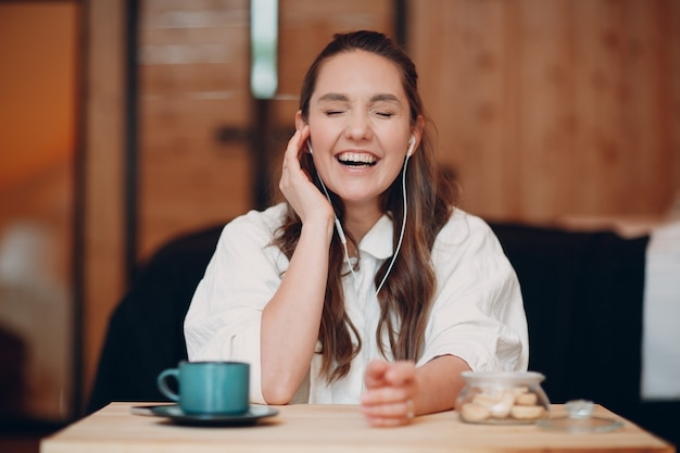 Laughing happy young woman sitting at table at home behind computer laptop and talking on video call girl female with portable mobile headphones speaking online on webcam indoors