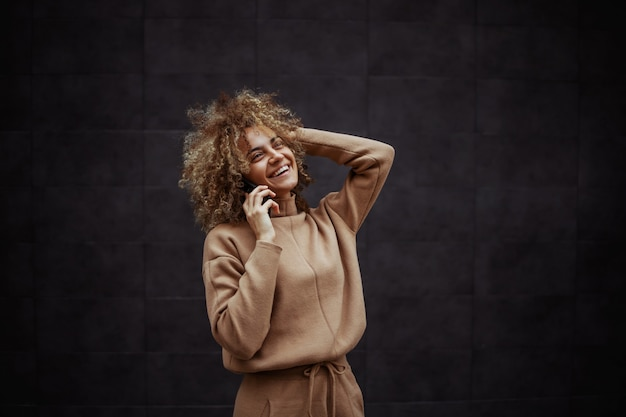 Laughing hip hop girl in tracksuit having phone call with her friend
