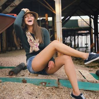 바다 해변의 오래된 부두 아래에서 힙스터 소녀 초상화를 웃고 있습니다.