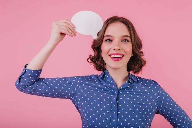 분홍색 벽에 서있는 어두운 눈을 가진 jocund 소녀를 웃 고있다. 뭔가 즐거운 생각을 세련된 곱슬 젊은 여자.
