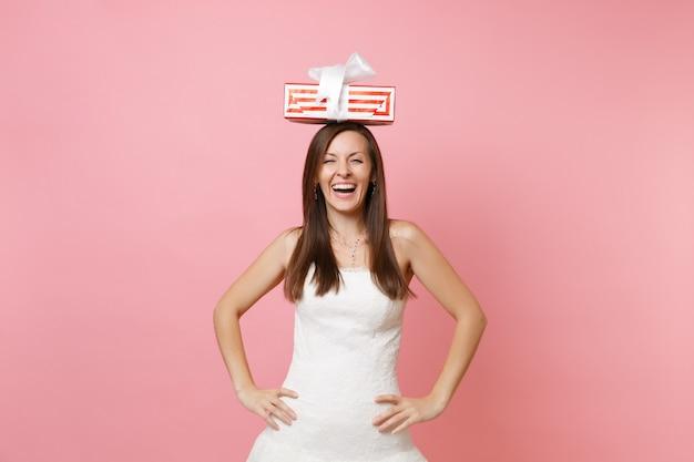 Ridendo gioiosa donna in abito bianco in piedi con le braccia sui fianchi, con in mano una scatola rossa con un regalo, presente sulla testa