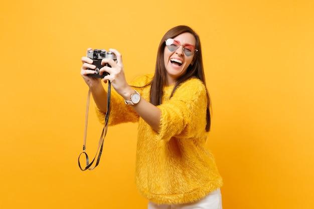 밝은 노란색 배경에 격리된 복고풍 빈티지 사진 카메라로 셀카를 찍는 하트 안경을 쓴 즐거운 젊은 여성이 웃고 있습니다. 사람들은 진심 어린 감정, 라이프 스타일 개념입니다. 광고 영역입니다.