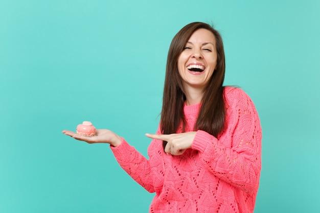 Смеющаяся радостная молодая женщина в вязаном розовом свитере, указывая указательным пальцем на торт в руке, изолированной на синем фоне бирюзовой стены студийный портрет. концепция образа жизни людей. копируйте пространство для копирования.