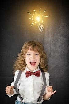 Смеющийся ребенок в классе. счастливый ребенок против доски. концепция образования