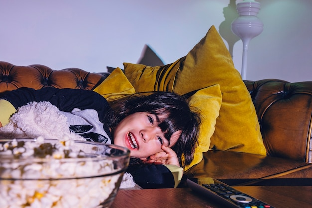 Laughing kid watching tv in dark