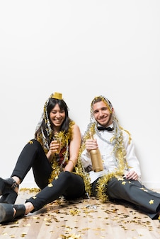 Laughing lady and guy in evening wear and tinsel with bottle and glass on floor