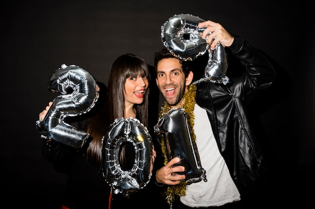 Laughing lady and guy with tinsel and balloons numbers