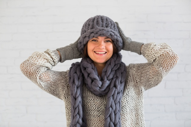 Laughing lady in mittens, hat and scarf