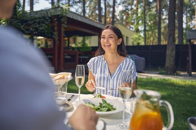 시골에서 따뜻한 날씨를 즐기면서 잘 생긴 남자와 식탁에 앉아 웃는 아가씨
