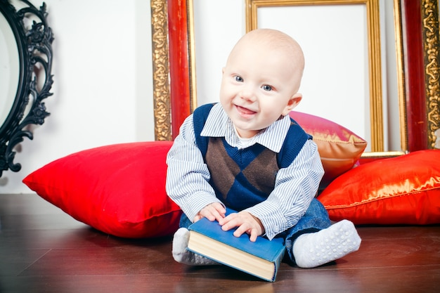 Laughing little baby with book
