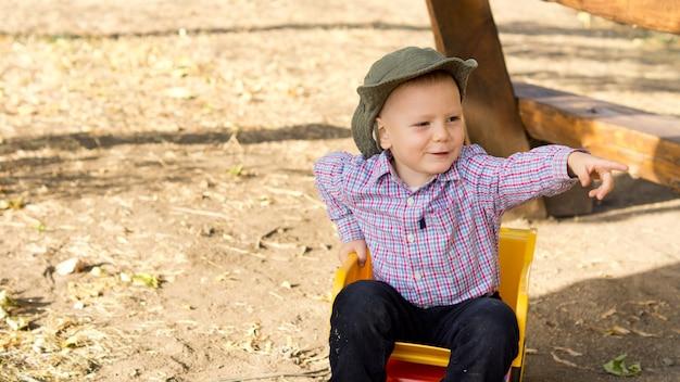 Смеющийся маленький мальчик сидит на улице в игрушечном самосвале, указывая пальцем за пределы кадра