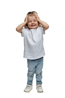 Laughing little girl 2-3 years old in jeans stands and holds her head. isolated on white background. verical. full height.