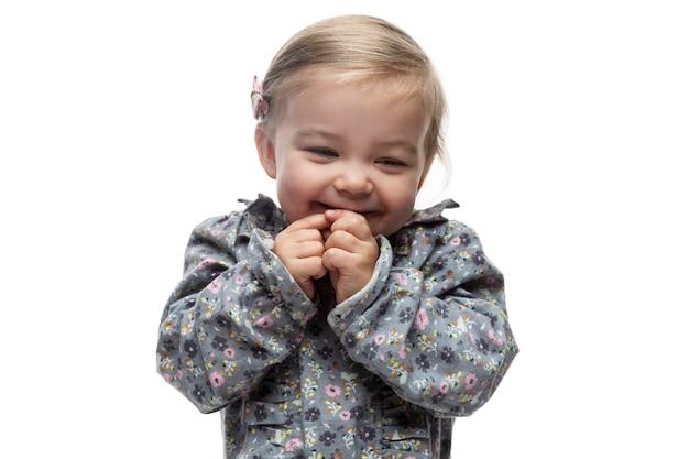 꽃무늬 드레스를 입고 3살 된 어린 소녀를 웃고 있습니다. 아이들에 대한 사랑, 부드러움 및 보살핌. 흰색 배경에 고립.