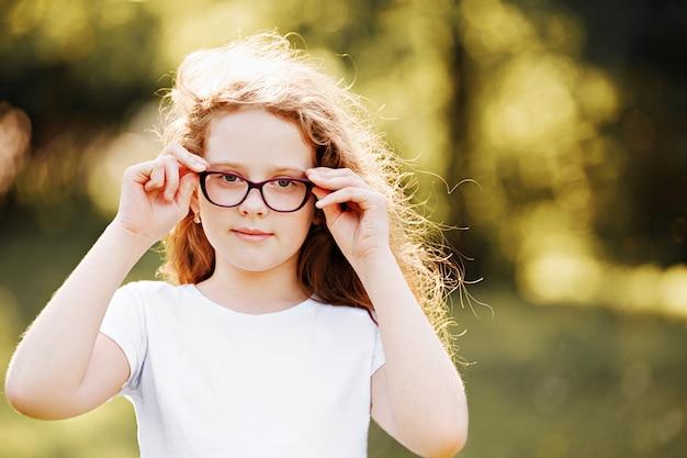Laughing little girl in eyeglasses in spring park.